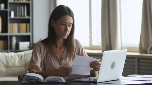 Frustrated shocked woman feeling upset reading bad news in letter Frustrated shocked young woman feel upset read bad news in paper letter sit at home office desk, stressed worried lady receive post mail notice about financial problem in bank debt bill tax invoice foreclosure stock videos & royalty-free footage