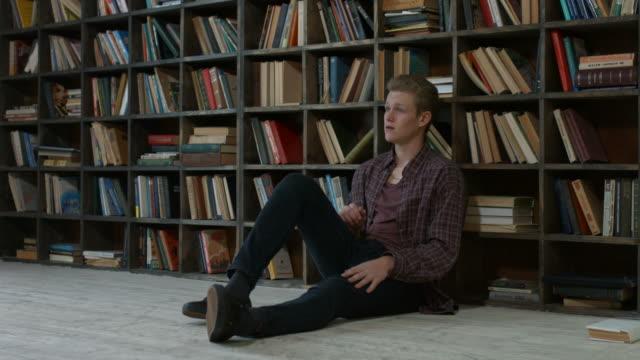 vídeos de stock e filmes b-roll de frustrated student having a lot to read in library - dureza