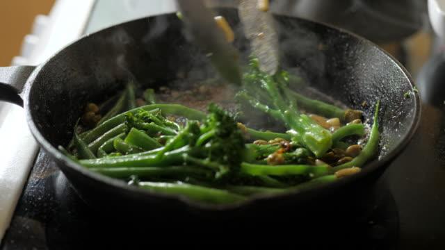ブロッコリーの茎、スライスしたニンニクとケッパーをスキレットパンに入れたグリーンビーンズを炒める - ベジタリアン料理点の映像素材/bロール