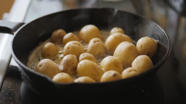 fry off new potato on skillet pan - молодой картофель стоковые видео и кадры b-roll