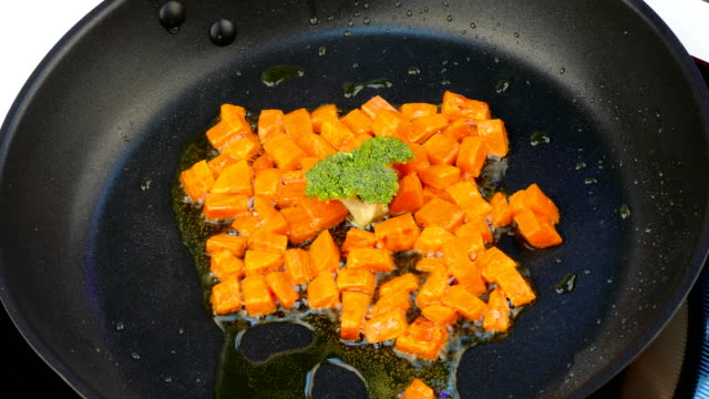 fry pieces of carrots in oil in a frying pan with broccoli video