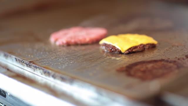 frying a cheeseburger - cheeseburger filmów i materiałów b-roll