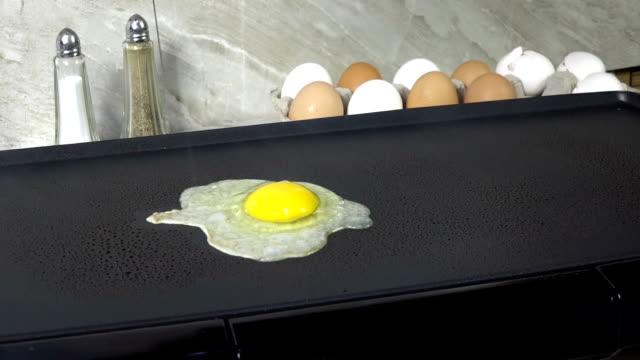 frying an egg - płyta do pieczenia filmów i materiałów b-roll