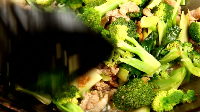Frying broccoli with pork in pan Thai chef frying chopped broccoli and chopped pork in pan, Thai food. stir fried stock videos & royalty-free footage