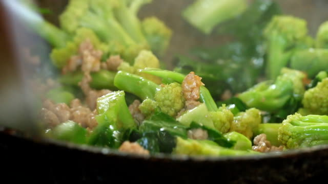 Frying broccoli with pork in pan Frying broccoli with pork in pan, outdoor Chiangmai Thailand stir fried stock videos & royalty-free footage