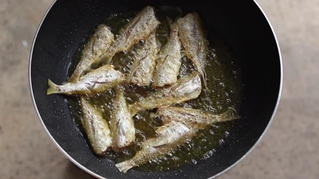frying fishes in frying pan. - tajska kuchnia filmów i materiałów b-roll