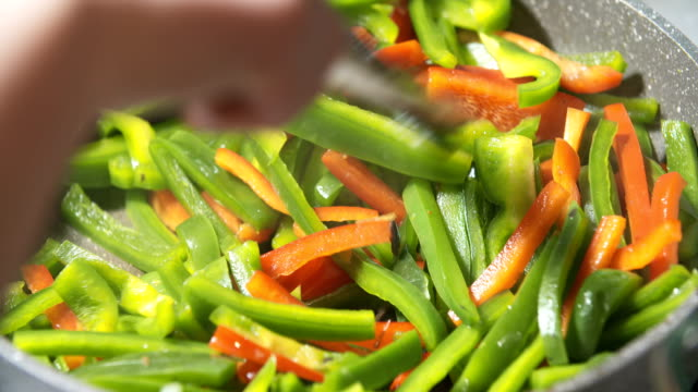 frying green and red pepper on pan