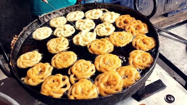 vidéos et rushes de . le jalebi de friture, un dessert indien de plat doux dans le sirop de sucre jusqu'à ce qu'il devienne brun doré - entonnoir