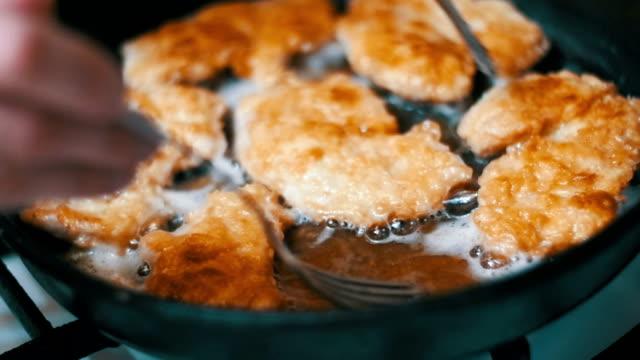 vídeos de stock e filmes b-roll de frying meat chops on a frying pan in the home kitchen. slow motion - produto de carne