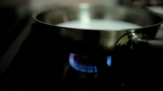 frying pan on stove in restaurant kitchen - padella pentola video stock e b–roll