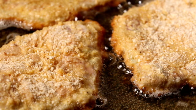 Frying pork meat coated with breadcrumbs in a pan video