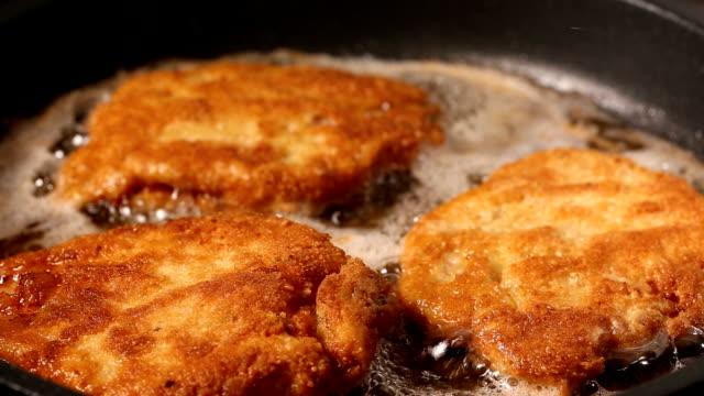 frying pork meat coated with breadcrumbs in a pan - сковорода стоковые видео и кадры b-roll