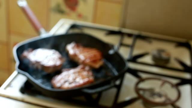 Frying rib eye steak in a frying pan