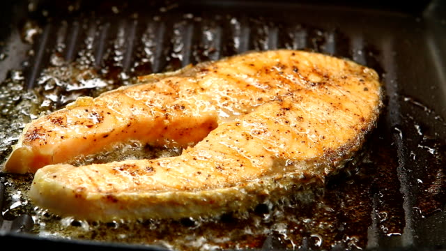 frying salmon steak in pan - articoli casalinghi video stock e b–roll