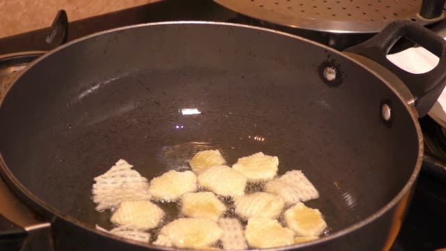Frying the fries with heated oil in the pan. Frying the fries with heated oil in the pan and stirring them. onion ring stock videos & royalty-free footage