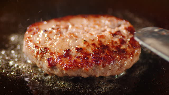 Frying the meat burger with a spatula on the pan. Frying the meat burger with a spatula on the pan. On a black background. juicy stock videos & royalty-free footage
