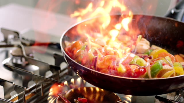 Frying vegetables and chicken Slow motion shot of frying food into the pan including flaming. Slow motion 200fps ARRI Amira shot cooking pan stock videos & royalty-free footage