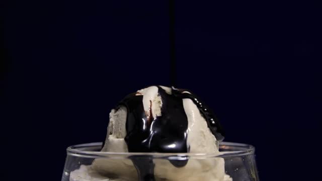 vídeos y material grabado en eventos de stock de sundae con salsa fudge (hd - glaseado para postres