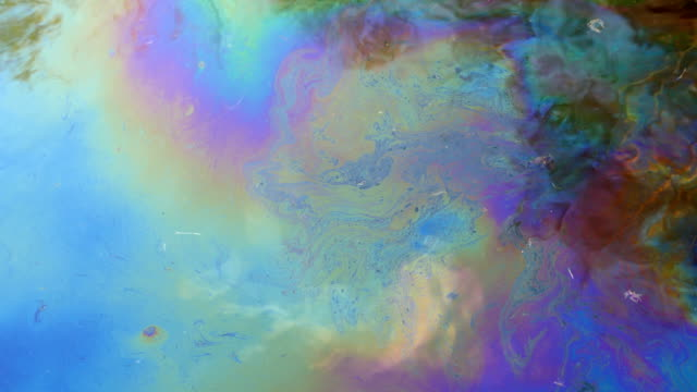 Fuel oil on water creating iridescent colours. - vídeo