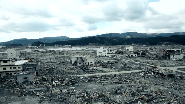 04/30/2011 Fukushima in Japan : aerial shot over the destroyed city and road under the sun Destroyed buildings and houses across the road after the tsunami in Japan. City of Fukushima is ravaged after the disaster, nothing in the city. No one in the town, an evacuate city. A lot of dust and trash under cloudy sky. Mountains in the background. earthquake stock videos & royalty-free footage