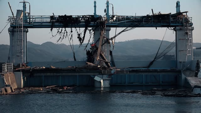 Fukushima, Japan - 03/11/2011 : destroyed harbor with mountains in the background after the tsunami