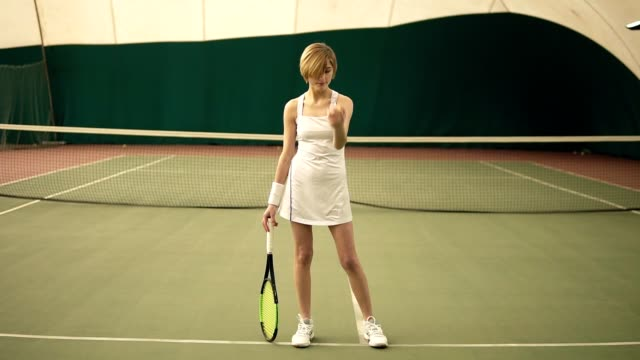 vídeos de stock e filmes b-roll de full body size portrait footage of a young attractive sportive woman with short blond hair wearing white sportswear, playing with the ball in covered tennis court - ténis calçado desportivo