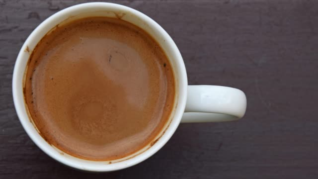 full cup of coffee with milk on table - gommapiuma video stock e b–roll