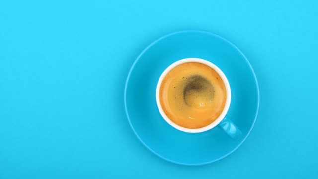 full cup of espresso coffee on blue - in cima video stock e b–roll