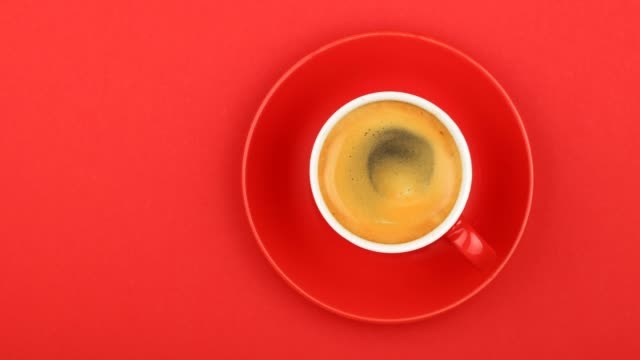 Full cup of espresso coffee on red