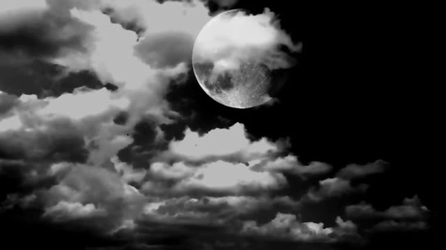 Full glowing grey moon with clouds being blown by winds during storm at nights.