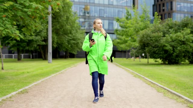 Full length front view shot of teenage female food courier in green uniform and with thermal bag walking down street, using gps app on smartphone and looking around while delivering order