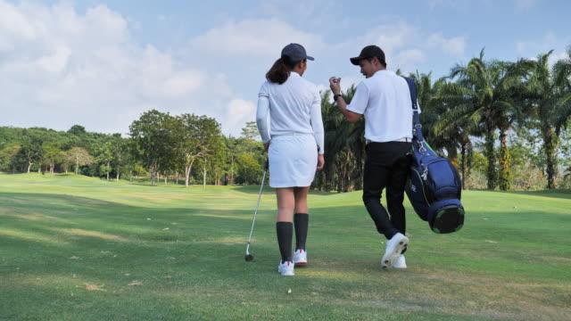 sağlıklı bir yaşam tarzı ile mutlu bir çift tam uzunlukta golf kıyafetleri giyen, yaz güneşli bir günde golf sahasına doğru profesyonel kulüpleri ile stand çanta taşırken - mountain top stok videoları ve detay görüntü çekimi