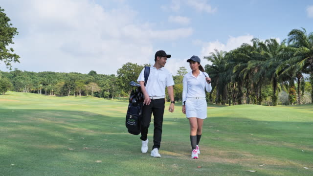 Full length of a happy couple with a healthy lifestyle wearing golf outfits, while carrying stand bags with professional clubs towards the golf course in a sunny day of summer