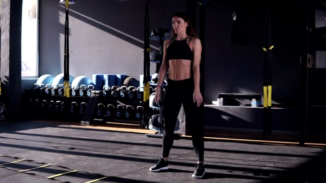 Full length of professional sportswoman in black sportwear doing exercise for butt muscles and legs. Attractive girl is practicing deep sit ups in modern gym