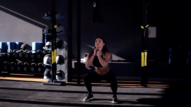 Full length of professional sportswoman in black sportwear doing exercise for butt muscles and legs. Attractive girl is practicing squats, sit ups in modern gym