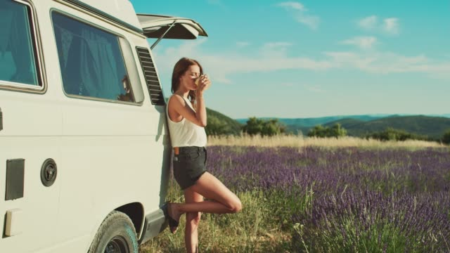 full length of woman against van enjoying coffee - ostrość na pierwszy plan filmów i materiałów b-roll