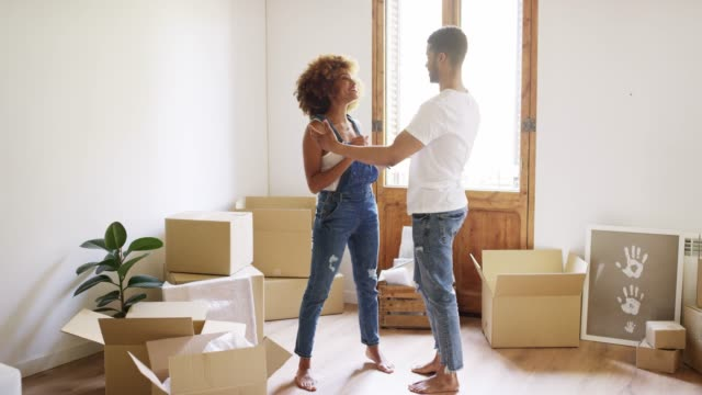Full length of young couple embracing at new home