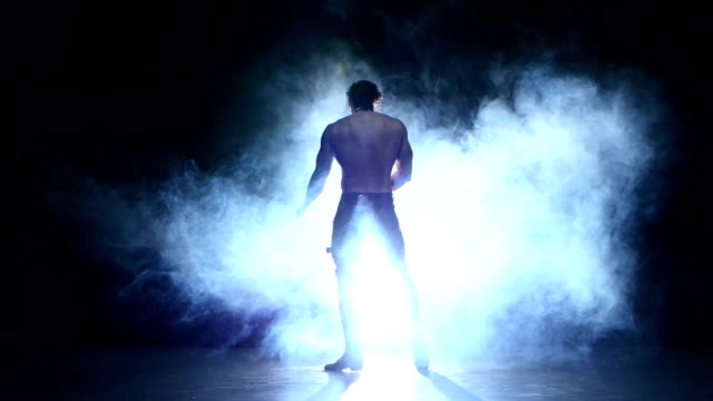 Full length silhouette of a young man dancer, smoke video