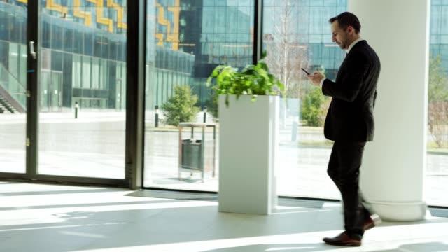 full längd spårning vänster skott av medelålders affärs man i formella kostym textmeddelanden på mobil telefon medan promenader för att arbeta längs entré hallen i moderna affärs centrum - kostym sida bildbanksvideor och videomaterial från bakom kulisserna