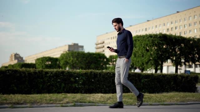 ポケットに手を入れて街の通りを歩きながら、携帯電話で自信のある若いビジネスマンのテキストメッセージの完全な長さの追跡ショット、サイドビュー - 全身点の映像素材/bロール