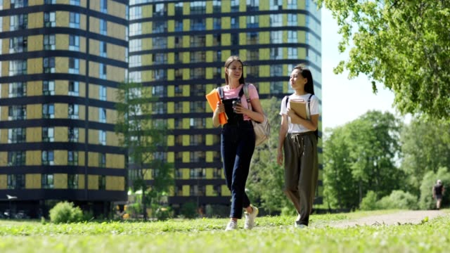 full length tracking shot of two diverse female college students, asian and caucasian, with backpacks, textbooks and binders talking and smiling while walking down street after classes - two students together asian video stock e b–roll