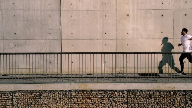 full length view with slow motion effect of male sportsman in white t-shirt running against urban concrete wall with empty copy space area for advertising - maglietta bianca video stock e b–roll
