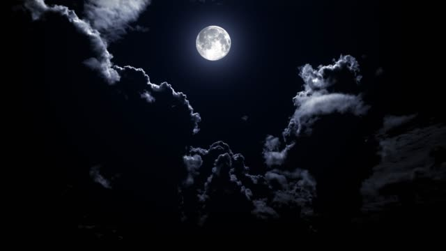 Full moon at night with time lapse clouds