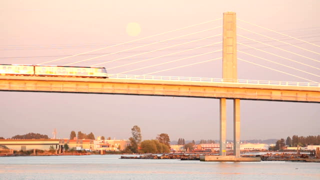 Full Moon, Canada Line Bridge, Vancouver New Canada Line rapid transit commuter trains, pass each other over the Fraser River from Richmond and Vancouver at dusk. The full moon rises in the background. british columbia stock videos & royalty-free footage