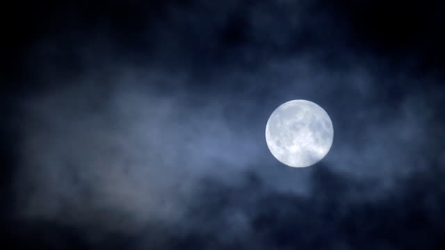 Full moon hiding by clouds on dark night sky background video