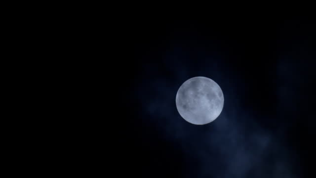 Full moon hiding by clouds on mist night sky background video