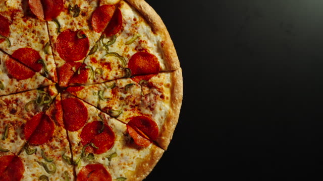 Full Pizza Is Rotating On A Black Surface In Left