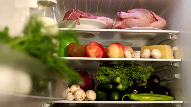 Full refrigerator of fresh healthy food. Slow mo. Open refrigerator with assortment of food and beverages. Fresh vegetables, fruit and meat on the refrigerator shelf. Close-up. fridge stock videos & royalty-free footage
