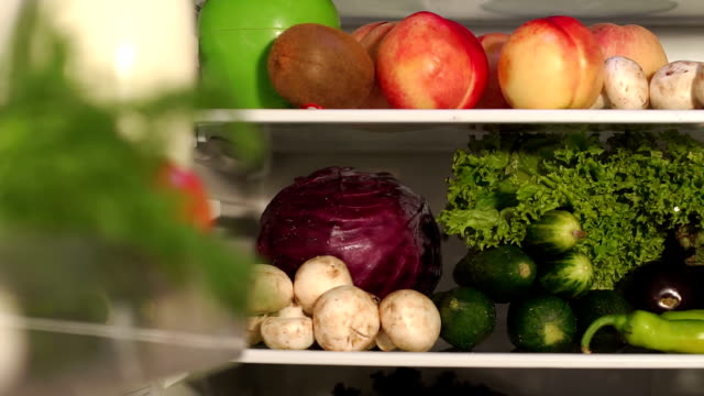 Full refrigerator of fresh healthy food. Slow mo. Fruits and vegetables on the shelves of the open refrigerator, close-up. Slow motion. Camera movement from left to right. fridge stock videos & royalty-free footage