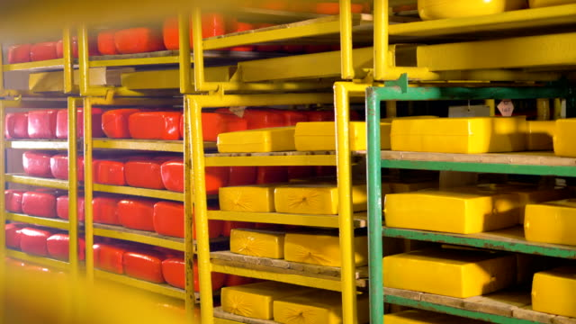 Full storage racks holding yellow and red cheese loaves. video